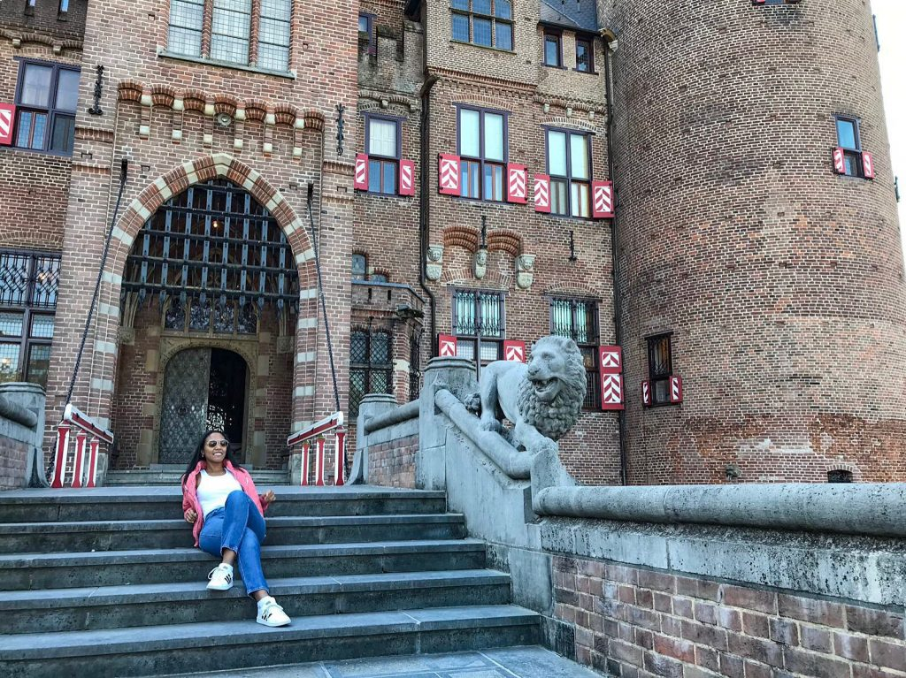 Girl sitting on castle steps at Kasteel de haar in Utrecht, Netherlands